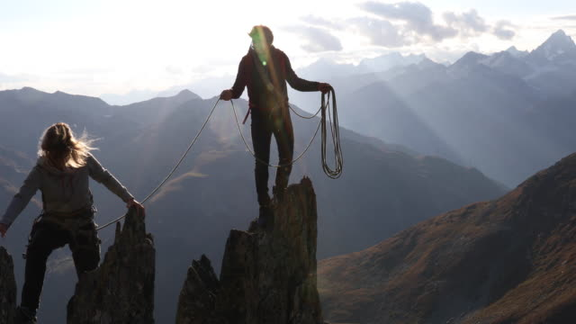 father belays daughter along knife edge ridge in mountains - rope stock videos & royalty-free footage