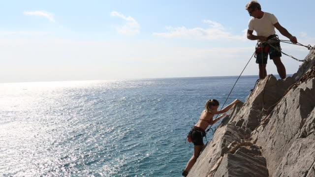 father belays daughter on rock climb above sea - corda video stock e b–roll