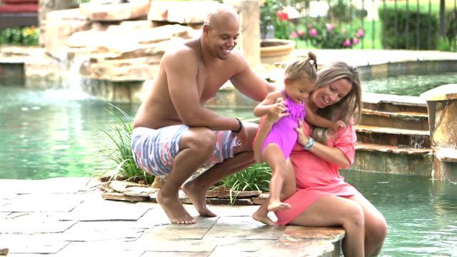 vídeos de stock e filmes b-roll de father brings little girl to sit beside mother at pool - família com um filho