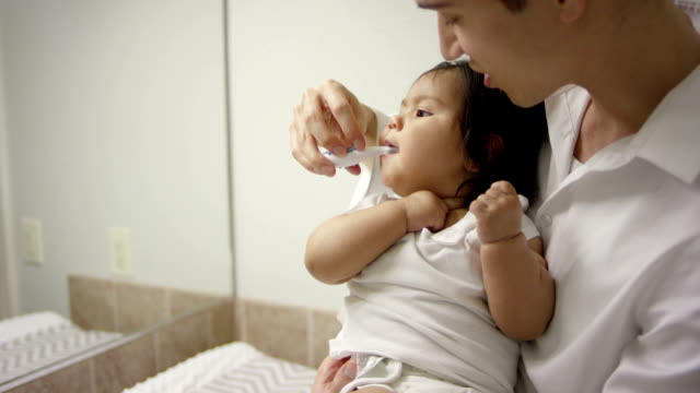father brushing babies teeth - brushing teeth stock videos & royalty-free footage