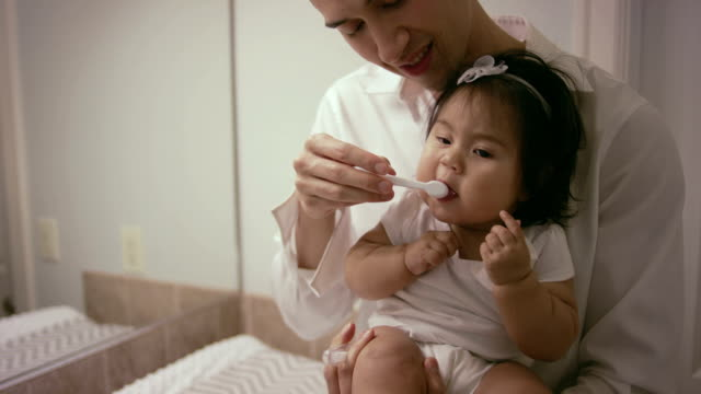 Father brushing babies teeth