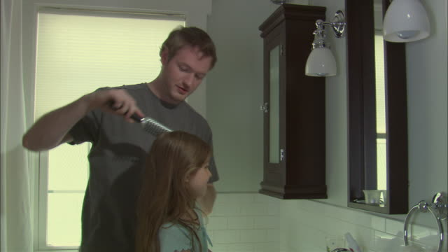 MS Father brushing girl's hair in bathroom / Westfield, New Jersey, USA