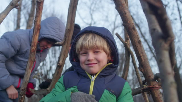 father building teepee with sons. riverside in the city - log stock videos & royalty-free footage