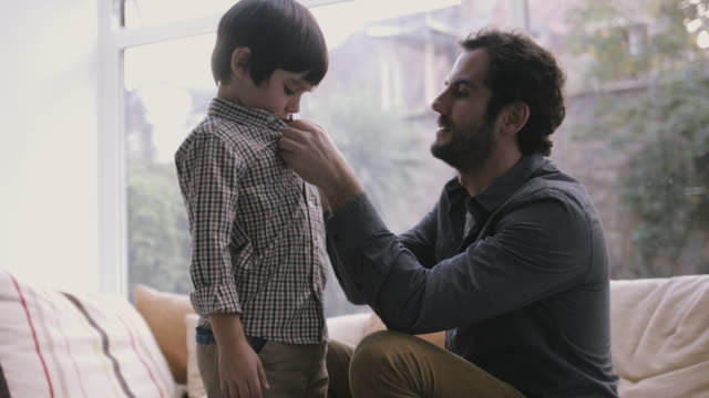 father buttoning little son's shirt - shirt stock videos & royalty-free footage
