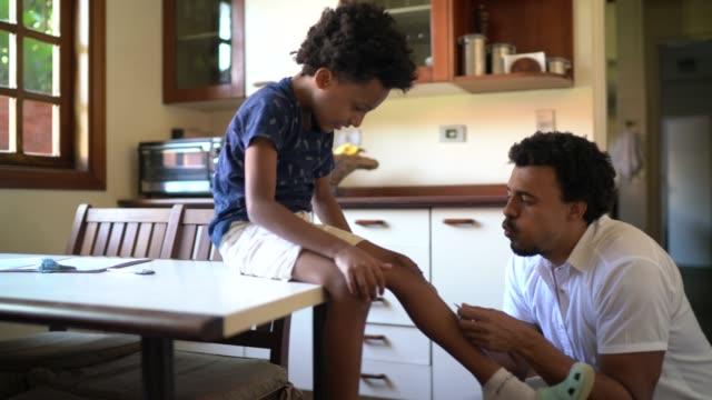 vídeos de stock, filmes e b-roll de pai se preocupa com seu filho após uma lesão em casa - son