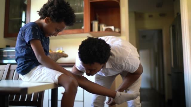 vídeos de stock, filmes e b-roll de pai se preocupa com seu filho após uma lesão em casa - dano físico