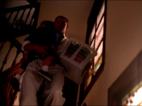 A father carries a laundry basket and a sleeping toddler down a staircase.