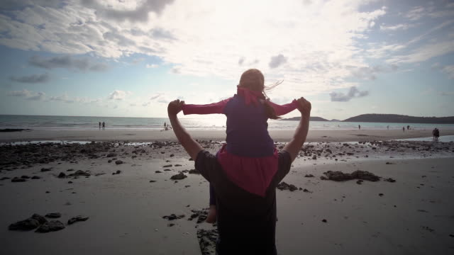 slo mo father carries daughter on shoulders walking on the beach - fathers day stock videos & royalty-free footage