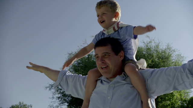 vídeos de stock, filmes e b-roll de a father carries his son on his shoulders and they play superheroes. - heróis