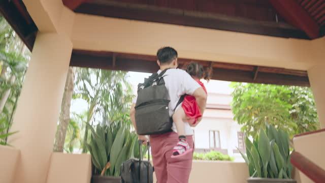 vídeos y material grabado en eventos de stock de el padre lleva equipaje mientras sostiene a su hija. - genderblend