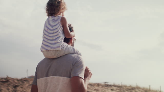 father carrying baby boy on shoulders on sand dune to beach - vertrauen stock-videos und b-roll-filmmaterial
