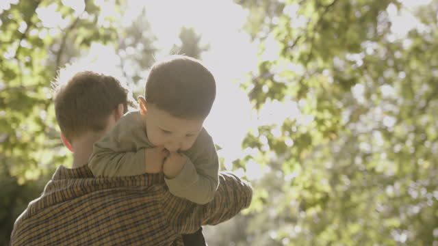 father carrying baby boy son in park in autumn and comforting - natural parkland stock videos & royalty-free footage