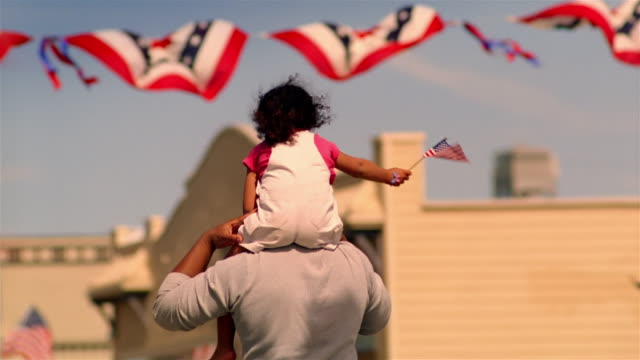 father carrying daughter on his shoulders / girl waves american flag / california - cultura americana video stock e b–roll