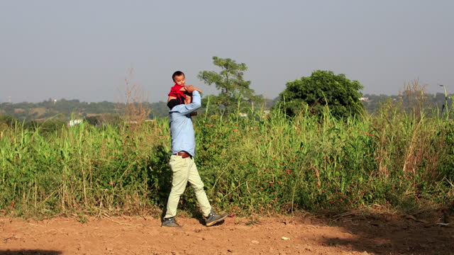 father carrying his baby daughter on shoulders - sorghum stock videos & royalty-free footage