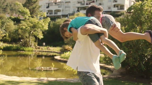 father carrying his children in park twirling them round. - famiglia con due figli video stock e b–roll