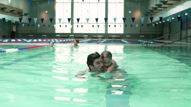 Father carrying his daughter on his back while swimming