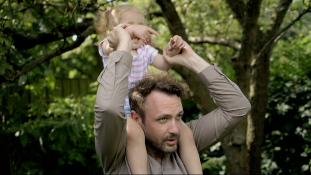 father carrying his daughter on shoulder in garden. - modern manhood stock videos & royalty-free footage