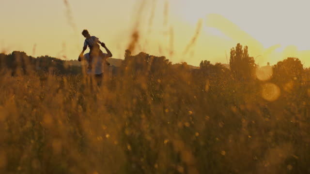 SLO MO Father carrying his son in grass at sunset