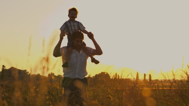SLO MO Father carrying his son on shoulders in meadow