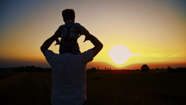 father carrying his son on shoulders - carrying on shoulders stock videos & royalty-free footage