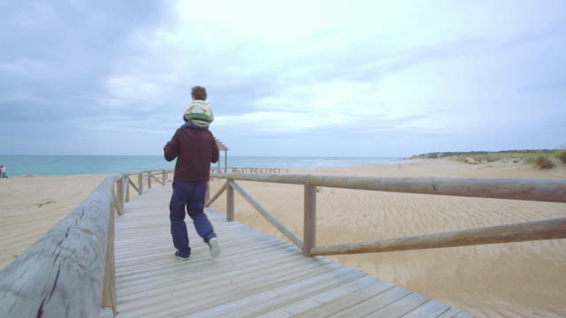 vídeos de stock e filmes b-roll de father carrying little boy on shoulders running in gangway in slow motion - carregar uma pessoa nos ombros