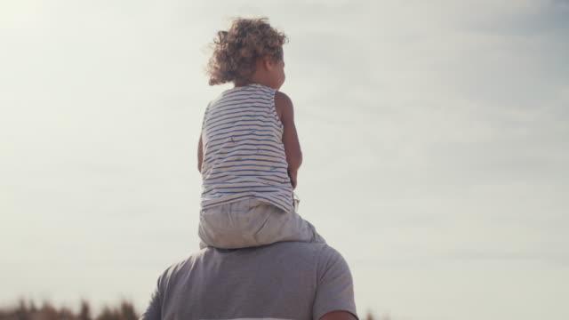 vidéos et rushes de father carrying playful baby boy on shoulders on sand dune - affectionate