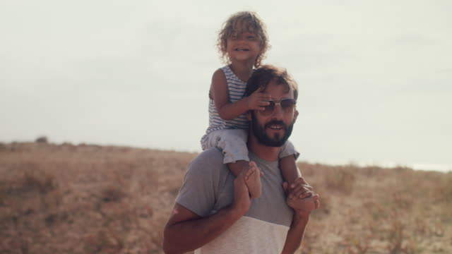 father carrying playful, smiling baby boy on shoulders - vertrauen stock-videos und b-roll-filmmaterial