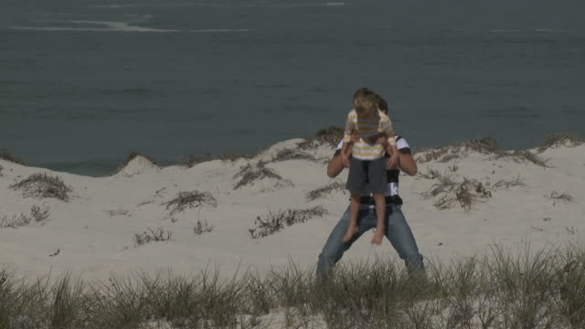 WS PAN Father carrying son (6-7) on shoulders at beach / Cape Town South Africa