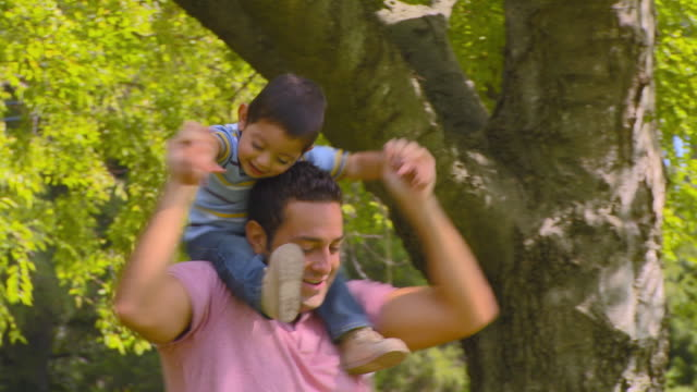 CU, PAN, Father carrying son (18-23 months) on shoulders, Richmond, Virginia, USA