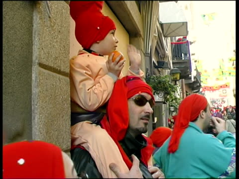 MS Father carrying son on shoulders, standing on street awaiting Battle of Oranges / Ivrea, Torino, Italy / AUDIO