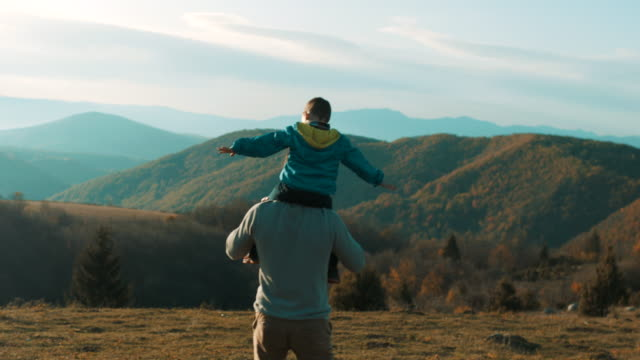 vídeos de stock e filmes b-roll de father carrying son on shoulders - acampar