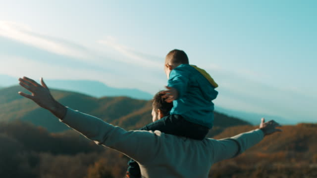 vídeos de stock e filmes b-roll de father carrying son on shoulders - horizontal