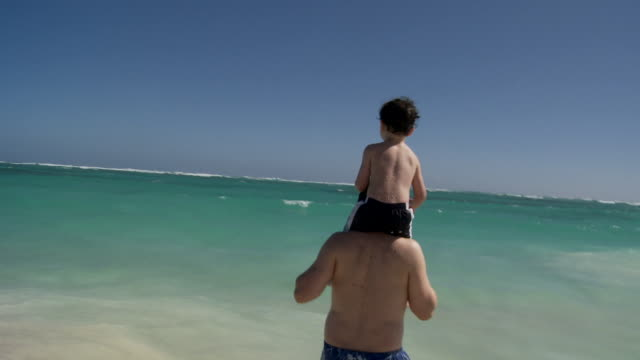 CU, WS, father carrying son (2-3) on shoulders, wading in ocean waves, Punta Cana, Dominican Republic