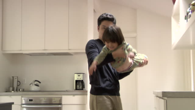 MS, PAN, Father carrying son (4-5) playing airplane in kitchen