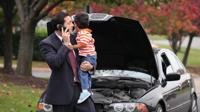 vidéos et rushes de ms father carrying son (2-3), talking on mobile phone standing by broken down car / richmond, virginia, usa - panne de voiture