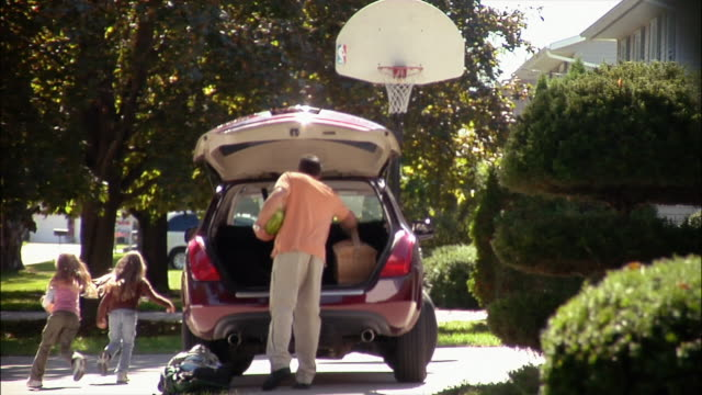 Father carrying supplies to car in driveway and loading into trunk assisted by daughters