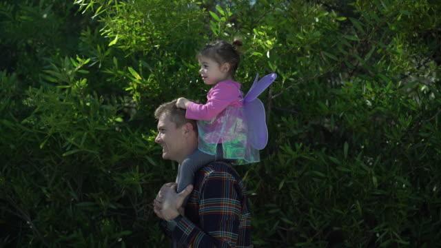 vidéos et rushes de ms sm father carrying young daughter on his shoulders. - se déguiser