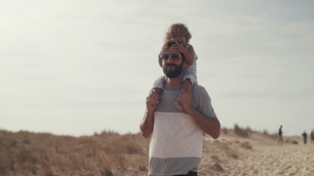 Father carrying young son on shoulders on sand dune, smiling