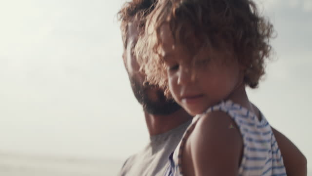 father carrying young son on the beach - kleinstkind stock-videos und b-roll-filmmaterial