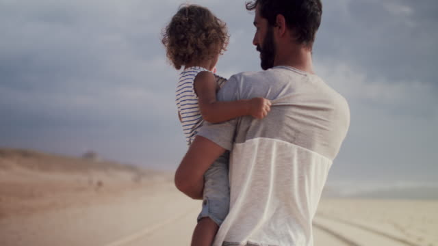 father carrying young son on the beach - males stock videos & royalty-free footage