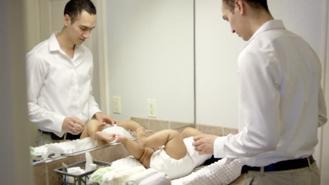 father changing babies diaper - diaper stock videos and b-roll footage