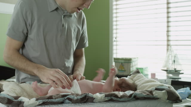 vídeos de stock, filmes e b-roll de ms zo father changing baby boy's diaper in nursery / lehi, utah, usa - lehi