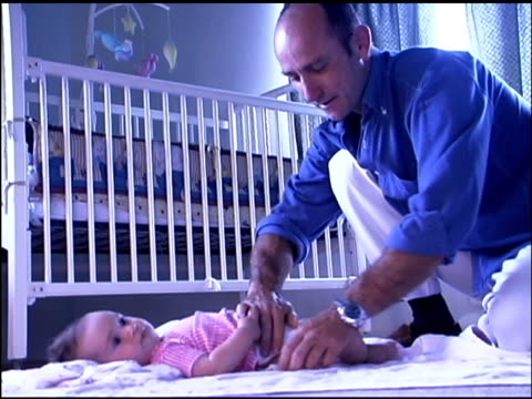 stockvideo's en b-roll-footage met father changing baby daughter's diaper - genderblend