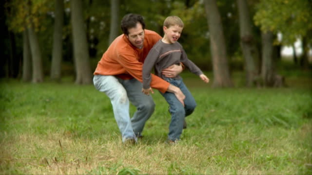 MS SLO MO Father chases after son (10-11), picks him up and swings him around / Wilmington, Illinois, USA
