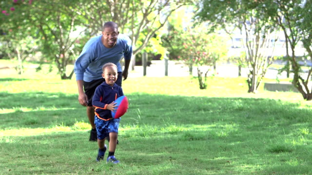 Father chasing little boy carrying football