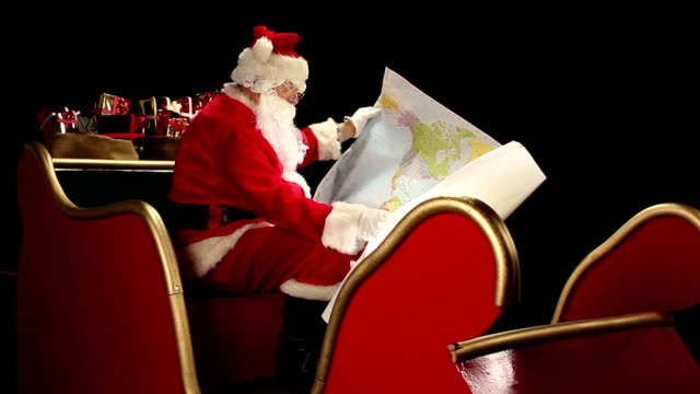 Father Christmas looking at world map