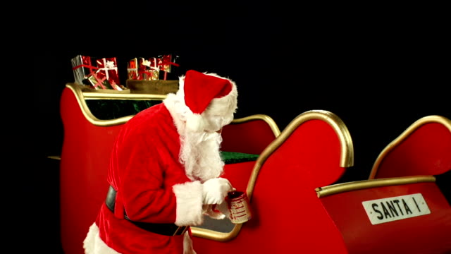 Father Christmas, Santa painting his sleigh ready for use