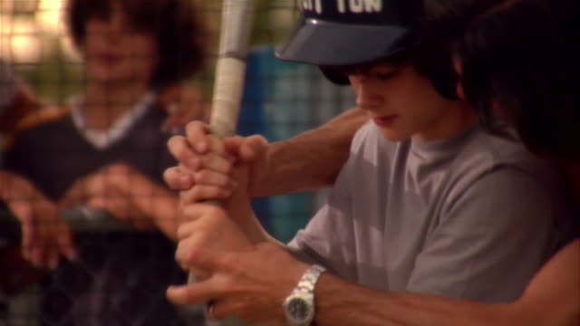 father coaching son in batting cage - batting stock videos & royalty-free footage