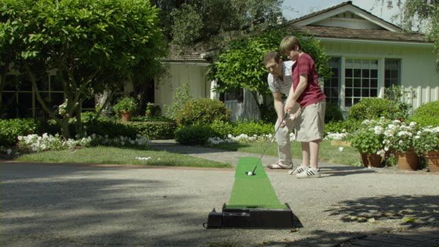 ms father coaching son (10-11) playing mini golf in garden, encino, california, usa - minigolf stock-videos und b-roll-filmmaterial