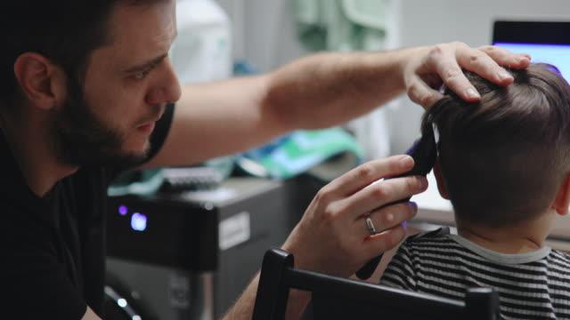 vídeos y material grabado en eventos de stock de padre cortando el pelo de su hijo en casa - familia con un hijo
